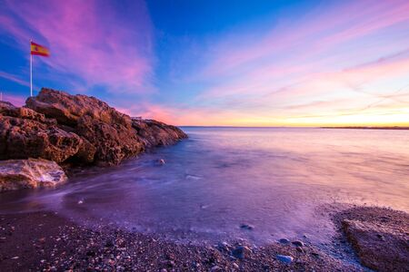 beautiful colorful sunset at rocky beach in spain Stock fotó