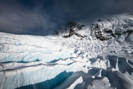 View from abouve at Franz Josef Glacier. West Coast, South Island, New Zealand. Aerial shot. Dark clouds in the background