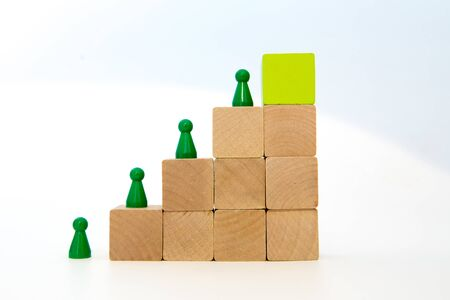 green meeple on wood block step stair. green block on top. Ladder career path concept for business growth success process, Copy space and white background 写真素材