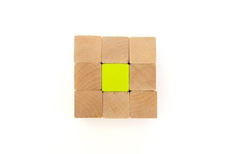 natural wooden blocks around green block with cup in the middle, white background, space for copy 免版税图像