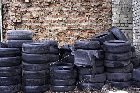 stocked: Old used tires stocked for recycling at red brick wall