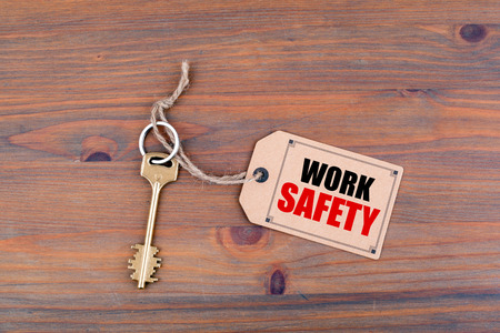 Key and a note on a wooden table with text - Work Safety.