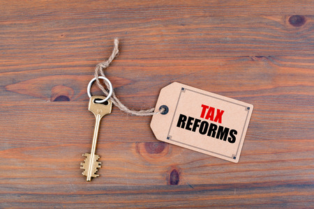Key and a note on a wooden table with text - Tax Reforms. Imagens - 66567606