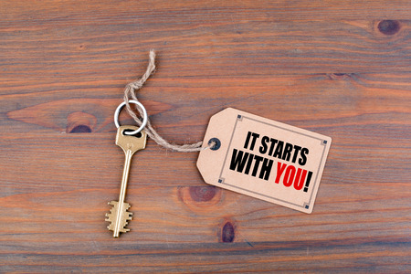 Key and a note on a wooden table with text - It Starts With You!
