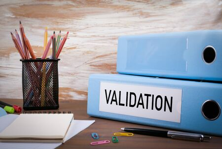 Validation, Office Binder on Wooden Desk. On the table colored pencils, pen, notebook paper.