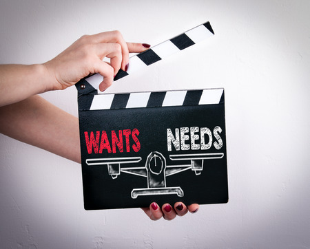 need direction: Wants and Needs Balance. Female hands holding movie clapper.