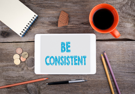 Be Consistent. Text on tablet device on a wooden table.