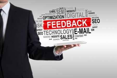 commenting: Feedback concept. Man holding a tablet computer. Stock Photo