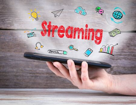 streaming: Streaming concept. Tablet computer in the hand. Old wooden background. Stock Photo