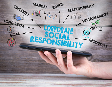Corporate Social Responsibility Concept. Tablet computer in the hand. Old wooden background.