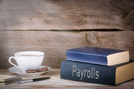 deductions: Payrolls. Stack of books on wooden desk.