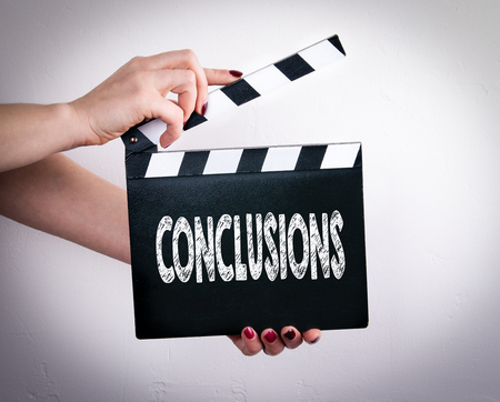 Conclusions. Female hands holding movie clapper. Gray background. Standard-Bild