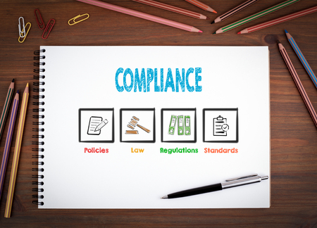 compliant: Compliance. Notebooks, pen and colored pencils on a wooden table. Stock Photo