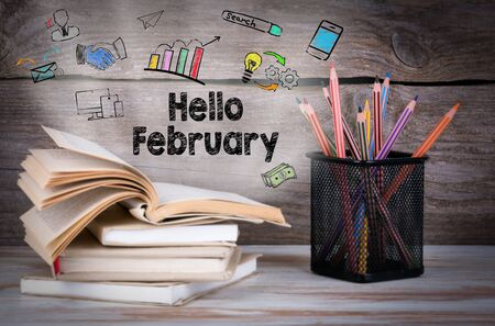 hi end: Hello February, Business Concept. Stack of books and pencils on the wooden table. Stock Photo