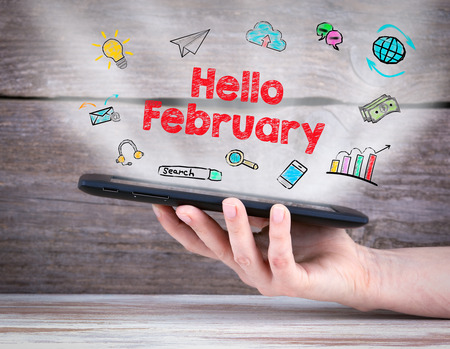 hi end: Hello February. Tablet computer in the hand. Old wooden background.