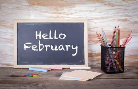 hi end: Hello February. Text on a blackboard. Old wooden table with texture. Stock Photo