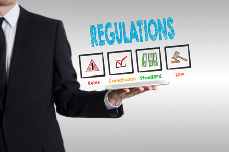 Regulations concept. Man holding a tablet computer, gray background