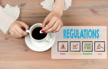 regulate: Regulations. Coffee cup top view on wooden table background.  Stock Photo