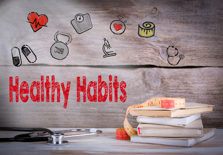 habitos saludables: Healthy habits Concept. Stack of books and a stethoscope on a wooden background. Foto de archivo