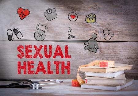 educacion sexual: Salud sexual. Pila de libros y un estetoscopio sobre un fondo de madera. Foto de archivo