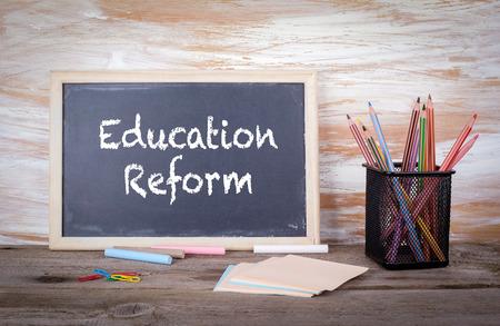 黒板に教育改革のテキスト。質感と古い木製のテーブル。