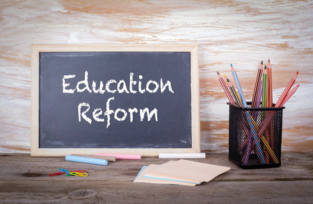 Education Reform text on a blackboard. Old wooden table with texture. Archivio Fotografico