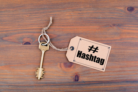Key and a note on a wooden table with text: Hashtag.