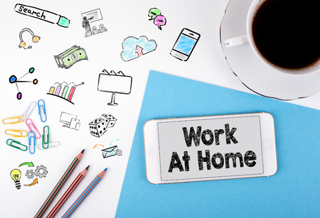 homeoffice: Work At Home. Mobile phone and coffee cup on a white office desk. Stock Photo