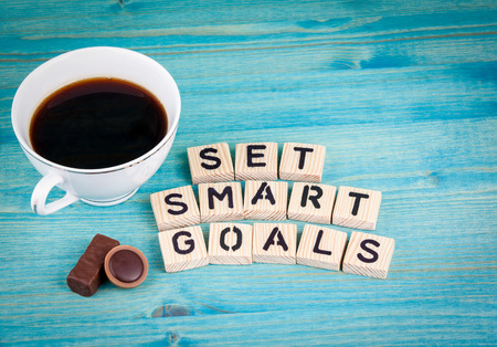 set smart goals. Coffee mug and wooden letters on wooden background.