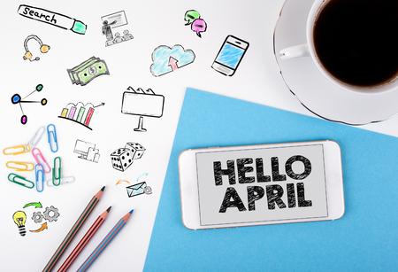 Ciao aprile, concetto di business. Telefono mobile e tazza di caffè su una scrivania bianca.