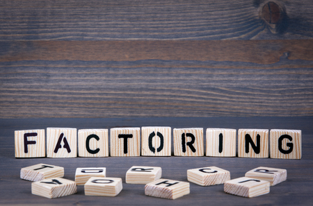 Factoring word written on wood block. Dark wood background with texture.
