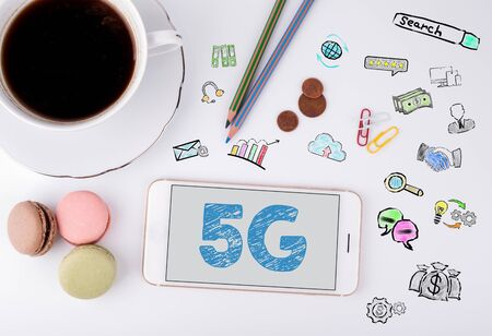 4g: 5g Business Concept. Mobile phone and coffee cup on a white office desk.