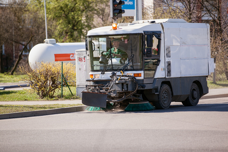 truck driver: Riga, Latvia - May 5, 2017: Sweeper vehicle sweeping the street.
