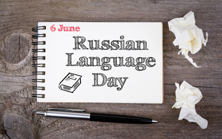 old notebook: 6 june Russian Language Day. Notebook and pen on the old wooden table.