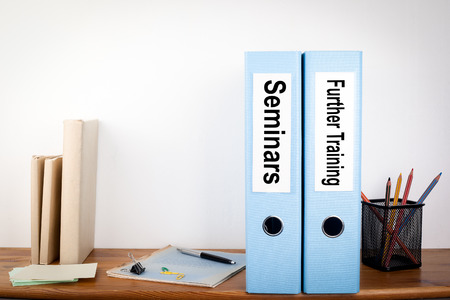further: Seminars and Further Training binders in the office. Stationery on a wooden shelf.