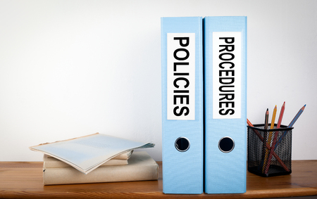 Policies and Procedures binders in the office. Stationery on a wooden shelf.