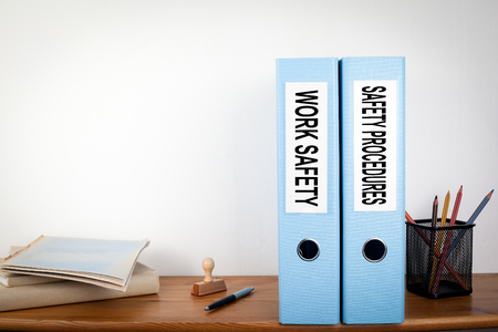 Work Safety and Safety Procedures binders in the office. Stationery on a wooden shelf. Banco de Imagens