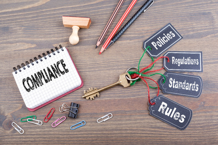 compliance consept. The key to success on a wooden office desk.