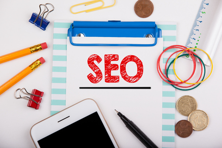 keyword research: seo concept. Office desk with stationery and mobile phone.