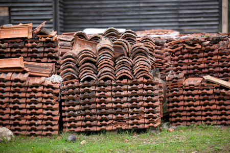 old clay tile roof tiles stacked on wooden pallets. The background for construction restoration and logistics. Stock Photo