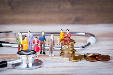 Medical care and expenses, health insurance. Colorful Human miniatures. Banco de Imagens