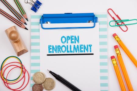 insurer: Open Enrollment. White office desk with stationery.