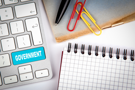 education policy: Government concept. Computer keyboard on a white office desk with various items.