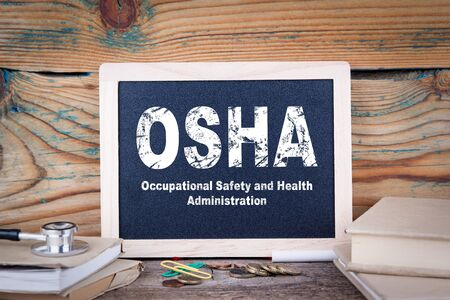 osha, Occupational Safety and Health Administration. Chalkboard on a wooden background. Stock Photo
