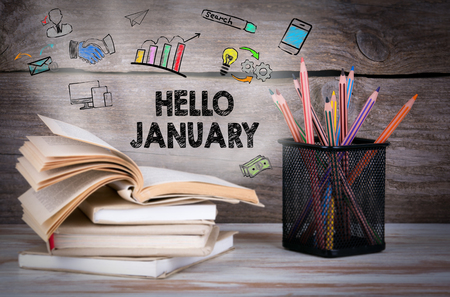 hello january, Business Concept. Stack of books and pencils on the wooden table.