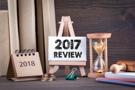 2017 review. Sandglass, hourglass or egg timer on wooden table showing the last second or last minute or time out
