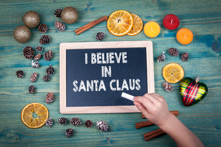 I Believe in Santa Claus. Christmas and holiday background. Ornaments and decor on a wooden table. Stock Photo