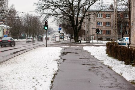 Latvia, Riga - December 1.2017: Wet snow in the city, traffic and people on the slippery streets. 報道画像