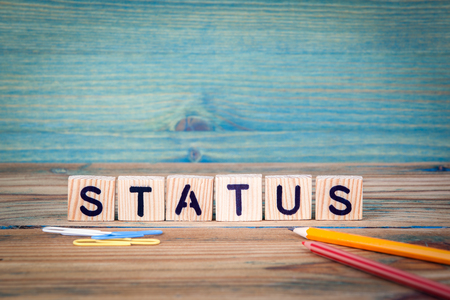 status - name from wooden letters. Office desk, informative and communication background.