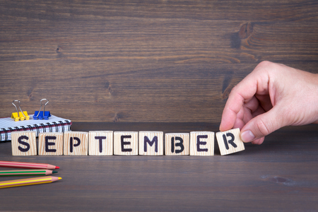 september. Wooden letters on the office desk, informative and communication background.